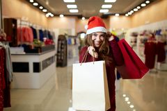 Happy girl shopping gifts in mall on christmas sale. New year holidays shopping idea concept. Smiling pretty caucasian royalty free stock image