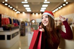 Happy girl shopping gifts in mall on christmas sale. New year holidays shopping idea concept. Smiling pretty caucasian royalty free stock photo