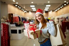 Happy girl shopping gifts in mall on christmas sale. New year holidays shopping idea concept. Smiling woman with royalty free stock images