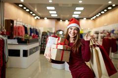 Happy girl shopping gifts in mall on christmas sale. New year holidays shopping idea concept. Smiling woman with stock image