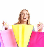 Happy girl shopping. Isolated on white background, excited young lady rejoices purchase, opening shopping bag and screams with pleasure, spending money with Royalty Free Stock Photo