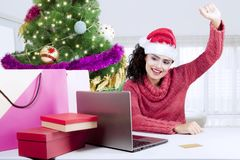 Happy girl shopping online at home. Pretty girl looks happy while shopping online by using a laptop near Christmas tree at home Royalty Free Stock Photography