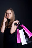 Happy girl with shopping talking on mobile phone. Photography studio Stock Image