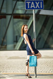 Happy girl with shopping waiting for taxi. Stock Images