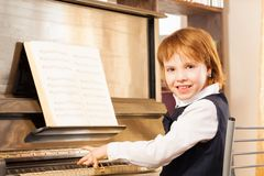 Happy girl with short hair playing the piano Royalty Free Stock Images