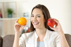 Girl showing apple and orange fruits. Happy girl showing apple and orange fruits sitting on a couch in the living room at home royalty free stock photography