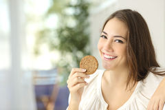 Happy girl showing a dietetic cookie Royalty Free Stock Photos