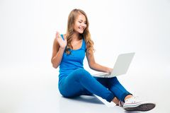 Happy girl showing greeting gesture at laptop Stock Images