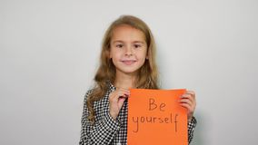 Happy girl showing handwritten words Be yourself on the orange sheet.  stock video