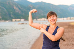 Happy girl showing muscles Stock Photography