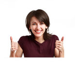 Happy girl showing OK. Beautiful, happy girl behind an empty sheet of paper showing OK with both hands royalty free stock images