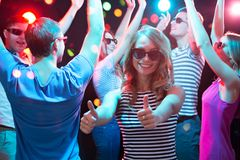 Happy girl showing OK sign in the night club stock image