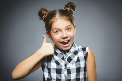 Happy girl showing thubs up. Closeup Portrait child smiling isolated on grey royalty free stock photos