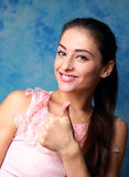 Happy girl showing thumb up. Success sign Stock Photos