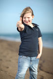 Happy girl showing thumbs up on the beach Royalty Free Stock Photography