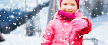Happy girl showing thumbs up over winter Stock Images