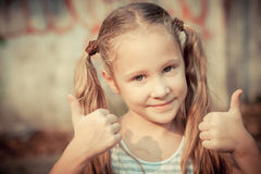 Happy girl shows gesture cool. At day time Stock Image
