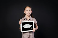 Happy girl shows screen of Digital Tablet with graduation cap Royalty Free Stock Photo