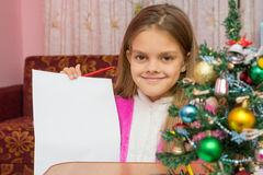 Happy girl shows a sheet of paper at table in a Christmas setting Stock Image