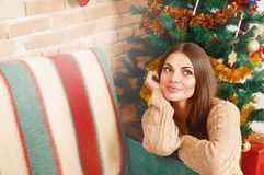 Happy girl sit under the Christmas tree and dream Royalty Free Stock Images