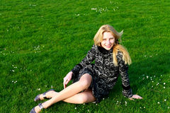 Happy girl sits on a blooming spring meadow Royalty Free Stock Photography