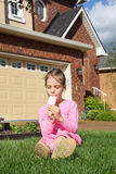 Happy girl sits on grass and eats ice cream. Happy girl sits on green grass near cottage and eats ice cream stock images