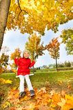 Happy girl sits on swings smiling during autumn Royalty Free Stock Image