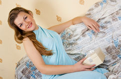 Happy girl sitting on bed Stock Photos