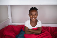 Happy girl sitting on bed at home Royalty Free Stock Photos