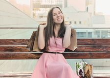Happy girl sitting on the bench, holding purchases in her hands Royalty Free Stock Photos
