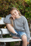 Happy girl sitting on the bench royalty free stock photography