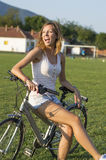 Happy girl sitting on bicycle on the football field Stock Photos