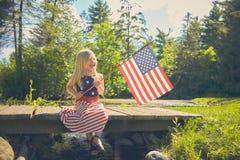 Happy girl sitting on bridge and waving American flag Royalty Free Stock Image