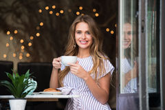 Happy girl sitting in the cafe and having breakfast with coffee and croissant. Beautiful smiling woman drinking coffee at the cafe and looking into the camera Stock Image