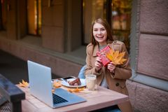 A happy girl sitting in a cafe, smiling and holding a gift box and autumn yellow. Outside. Royalty Free Stock Images