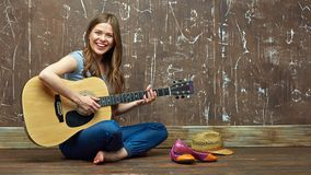 Happy girl sitting on floor with acoustic guitar. stock photo