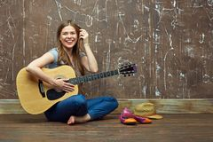 Happy girl sitting on floor with acoustic guitar. Stock Photos