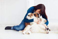 Happy girl sitting on the floor with caucasian shepherd puppies. Dogs stock photography