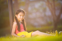 Happy girl sitting on grass in garden Royalty Free Stock Image