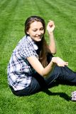 Happy girl sitting on the green grass Royalty Free Stock Images