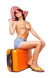 Happy girl sitting on her suitcase Stock Images