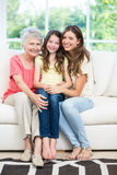 Happy girl sitting with mother and grandmother on sofa Stock Photo