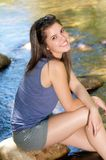 Happy girl sitting next to stream with feet in water Stock Photo