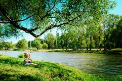 Happy girl sitting on river bank Royalty Free Stock Images