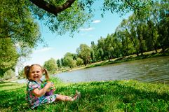 Happy girl sitting on river bank Royalty Free Stock Image