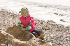 Happy girl sitting on a rock on sea coast and looking at the frame Royalty Free Stock Photography