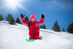 Happy girl sitting on sled on sunny day stock images