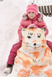 Happy girl sitting on a snowman. In winter royalty free stock photos