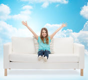 Happy girl sitting on sofa with raised hands Stock Photo