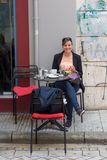 Happy girl sitting at street caffe. Royalty Free Stock Images